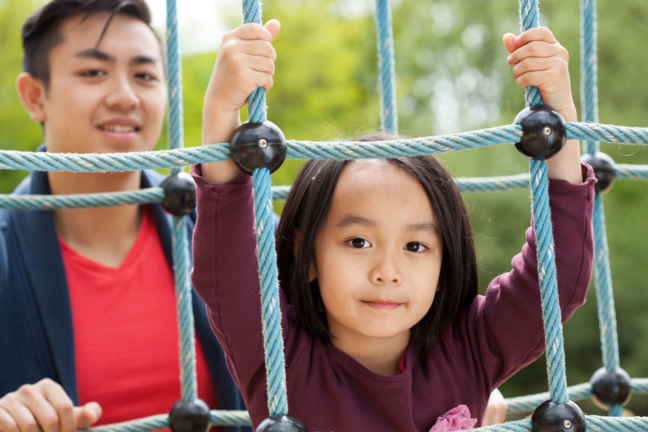 Asian dad and daughter on playground